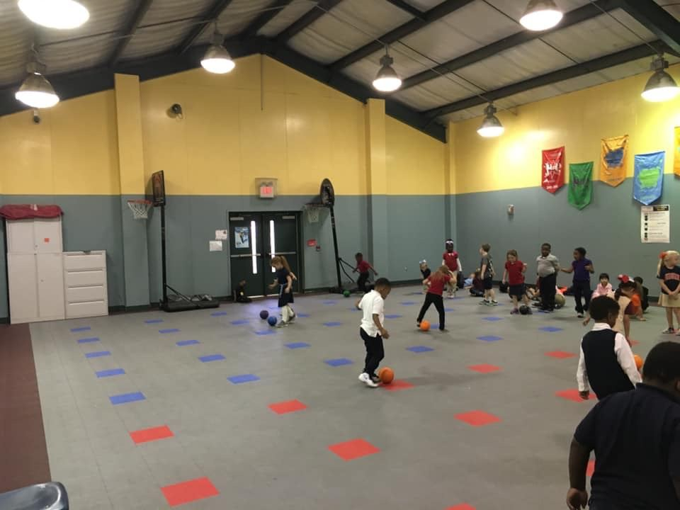 Kindergarten classes practicing dribbling skills